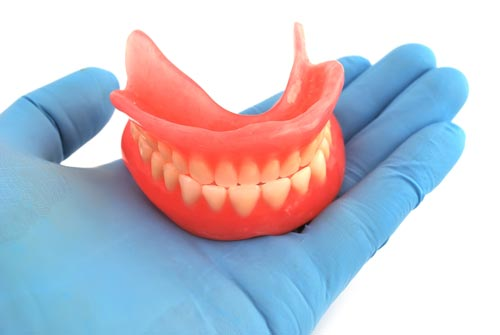 dentures held in a hand